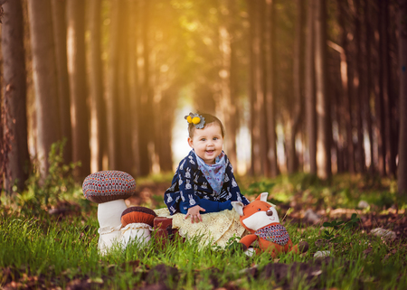 A little baby girl outdoors in front of a trees