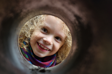 Little boy with curls looks through a pipe