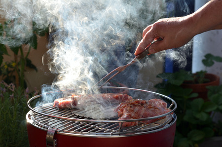 Hand turns marinated grill, which lies on a grate of a smoking grill. Stok Fotoğraf