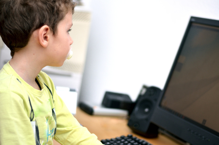 Child sits in front of a computer with a teat in his mouth Stok Fotoğraf