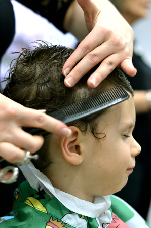 Small child sitting at the hairdresser's