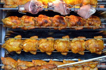 Gegrilltes Hähnchen und Schweinshaxe am Spieß