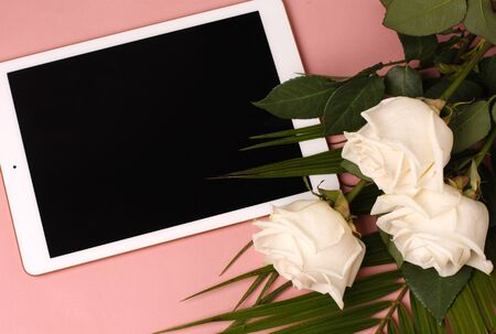 White roses and petals lying on a white surface. tablet with empty screen. Styled mock up top view on pale peach background. Device