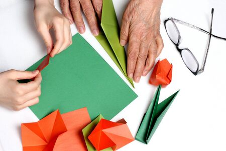 hands of a child and grandmother. they make origami tulips, different generations together