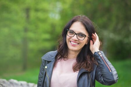 Beautiful middle-age woman in black leather jacket with glasses smiling broadly. Springtime, outdoors