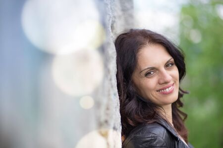 Beautiful middle-age woman in black leather jacket smiling broadly. Springtime, outdoors