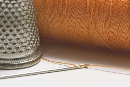 Orange sewing thread needle and thimble  Stock Photo