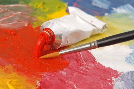Tube of red paint with a brush