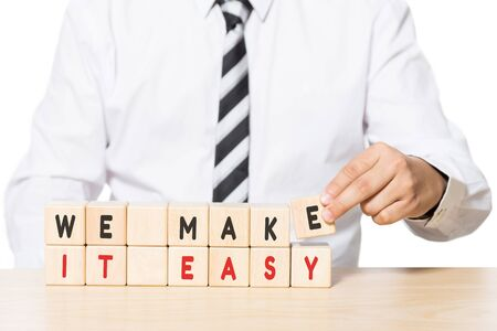 make belief: Close up Hand of a Businessman Arranging Wooden Blocks with we make it easy words on blocks