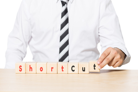 shortcut: Close up Hand of a Businessman Arranging Wooden Blocks with shortcut words on blocks