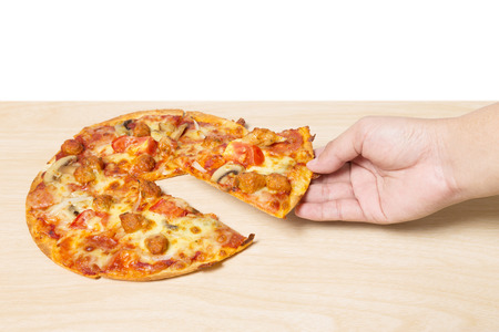 flavorful: hand holding tasty flavorful pizza on wood table Stock Photo