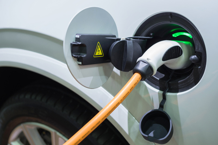 Charging an electric car with the power cable supply plugged in Stock Photo