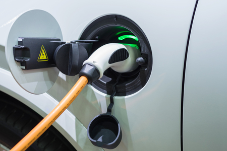 plugged in: Charging an electric car with the power cable supply plugged in Stock Photo