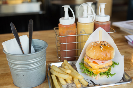 Hamburgers with beef, french fries, ketchup sauce and cheese in traditional buns, served on Stainless steel plate in shop background