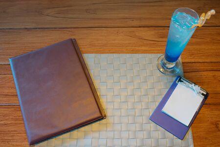 テーブル セット、メニューとビンテージのレストランで青い飲料