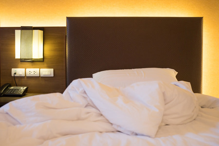 汚いベッド寝室のインテリアの装飾の上に白いシート枕、メッシー ベッド コンセプト 写真素材