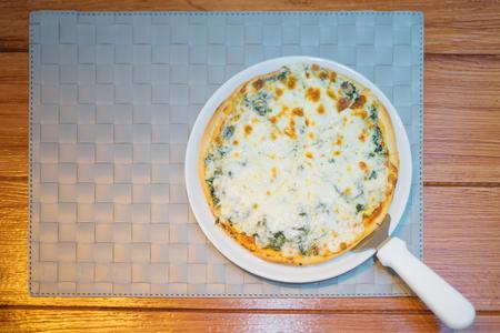 木材の背景にチーズとほうれん草のピザ イタリア料理