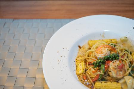 唐辛子とバジル白い皿の海の幸のスパゲッティ