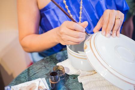 タイの女性使用ブラシ塗装デザイン、容器にタイの陶磁器の伝統芸術 写真素材