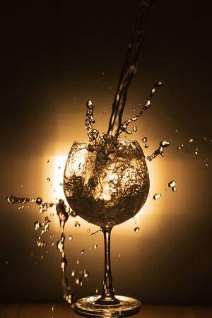 水のしぶきと暗い黒い背景にワイングラス
