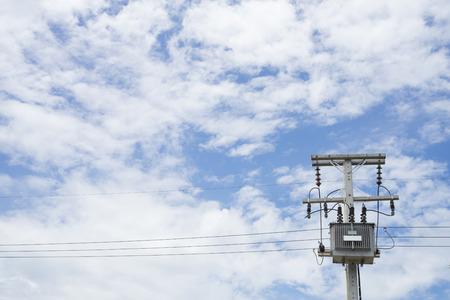 High voltage electrical transformer high on concrete poles, blue sky background