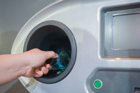 Reverse Vending Recycling Machine. Recycling machine that dispenses cash. Man hand puts plastic bottle to the machine Archivio Fotografico