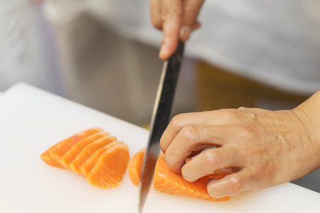 Hand of chef use knife preparing a fresh salmon on a cutting board, Japanese chef in restaurant slicing raw salmon, ingredient for seafood dish