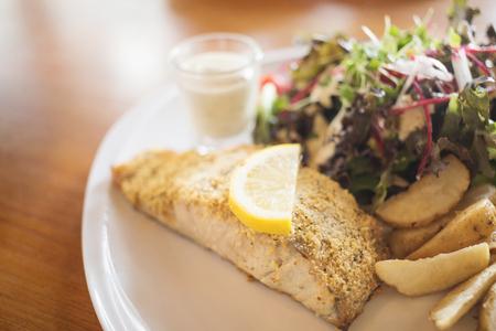 Roast fish steak fresh with potato and fresh vegetable salad on white plate