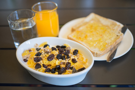 Breakfast served with water, orange juice, bread and jam, cereals milk and fruits. Balanced diet