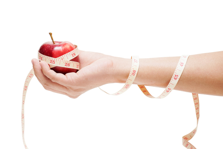 apple bind with measuring tape on hand isolated on white background, diet concept 写真素材