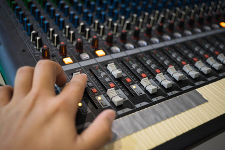 Hand on professional audio mixing console with faders and adjusting knobs, radio or TV broadcasting