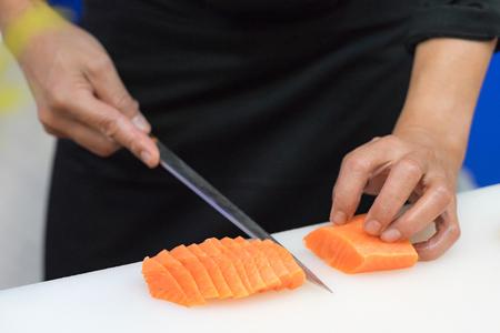 La mano dello chef usa il coltello che prepara un salmone fresco su un tagliere, chef giapponese nel ristorante che affetta il salmone crudo, ingrediente per il piatto di frutti di mare