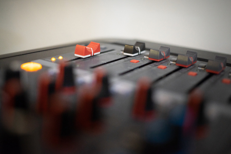 professional audio mixing console with faders and adjusting knobs, radio or TV broadcasting