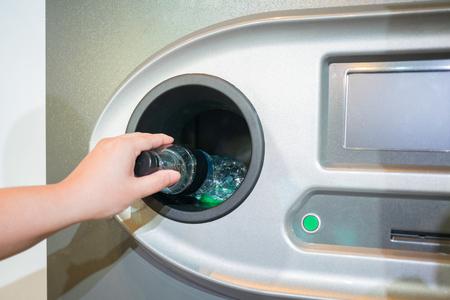 Reverse Vending Recycling Machine. Recycling machine that dispenses cash. Man hand puts plastic bottle to the machine 写真素材