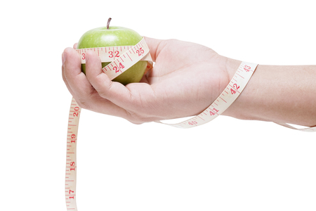 green apple bind with measuring tape on hand isolated on white background, diet concept