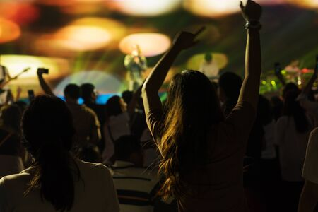 Crowd enjoying concert, happy people jumping, large group celebrating new year holiday, party background fun concept