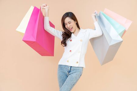 Portrait of Beautiful young smiling happy woman holding shopping bags isolated over orange background Reklamní fotografie
