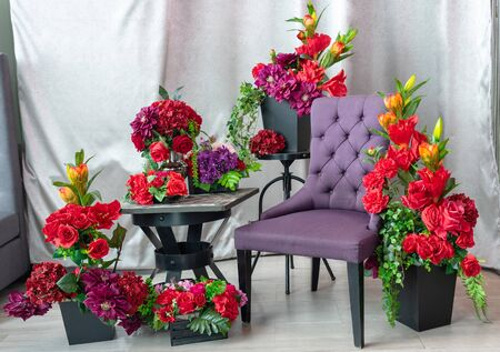 vintage chair and table with many red plastic flowers and plants, fabric background