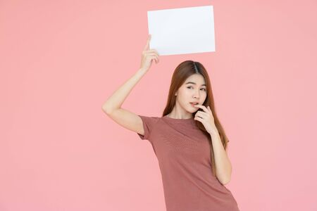 young asia smiling woman with long hair holding advertising sign board and pointing finger. Isolated portrait on pink background with copy space Reklamní fotografie