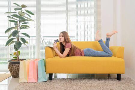 junge asiatische frau, die auf dem gelben sofa sitzt und laptop und kreditkarte verwendet, um online in der nähe von fenster und einkaufstasche einzukaufen?