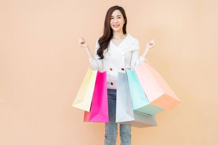 Portrait of Beautiful young smiling happy woman holding shopping bags isolated over orange