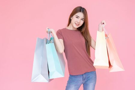 Portrait of Beautiful young smiling happy woman holding shopping bags isolated over pink background