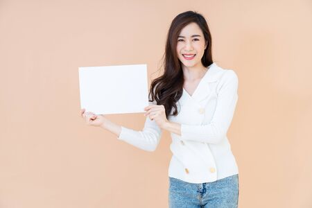 young asian smiling woman with long hair holding advertising sign board. Isolated portrait on orange background with copy space Reklamní fotografie