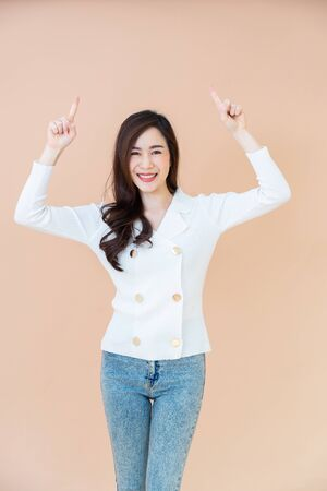 Young asia smiling woman with long hair pointing finger.