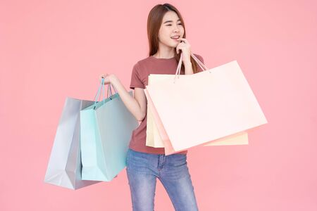 Portrait of Beautiful young smiling happy woman holding shopping bags isolated over pink