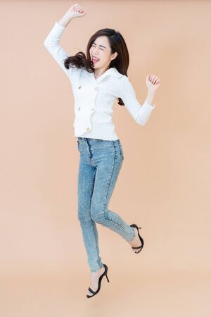 Full length portrait of cheerful positive pretty businesswoman jumping in the air with raised fists isolated on orange background. Life people energy concept