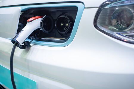 Charging an electric car with the power cable supply plugged in Reklamní fotografie