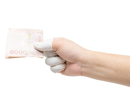 Hand in a fingertip glove holds money, protecting itself from an epidemic.