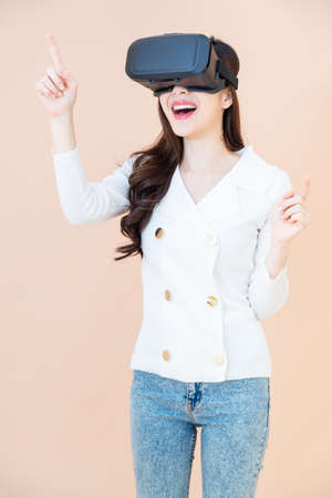 portrait of a young asia woman wearing a white cardigan and VR glasses. She is amazed by what she is seeing. Virtual reality headset. isolated on orange background Reklamní fotografie