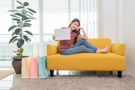 young asian smiling woman with long hair holding advertising sign board on the yellow sofa at home in living room near window and shopping bag Reklamní fotografie